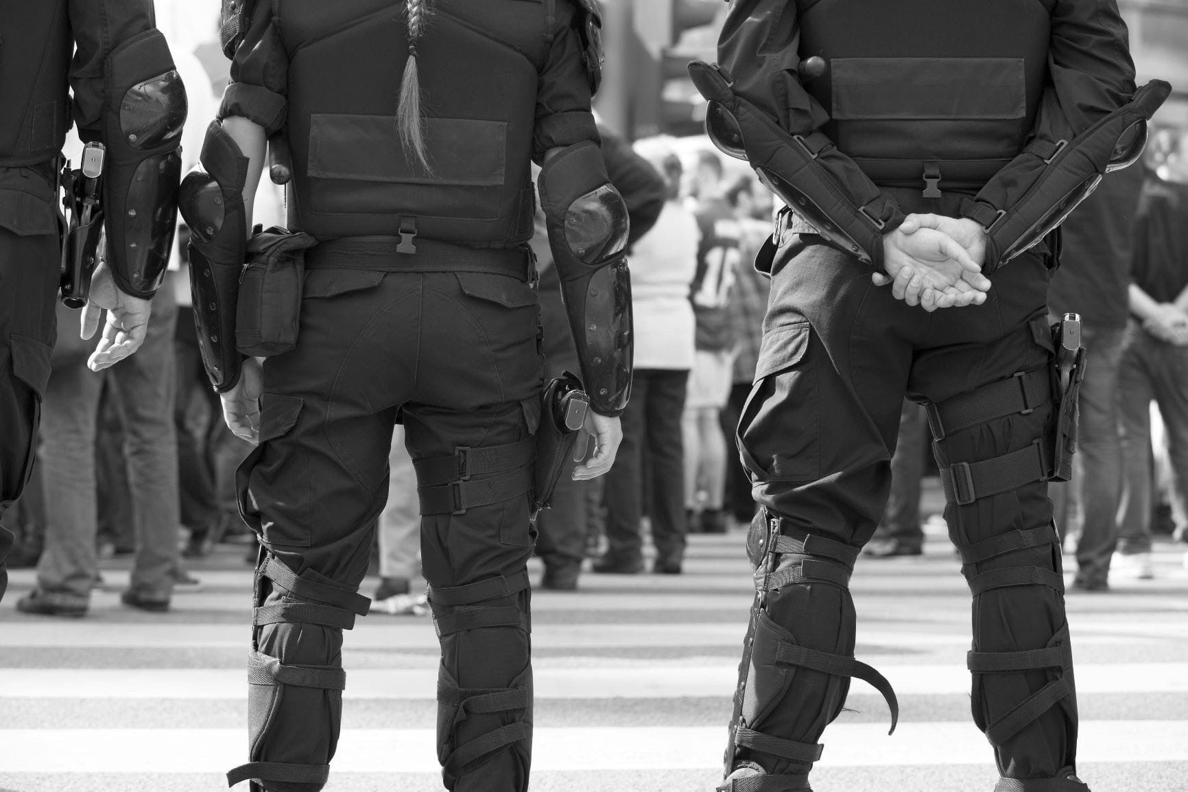 police officers facing a crowd and wearing body armor